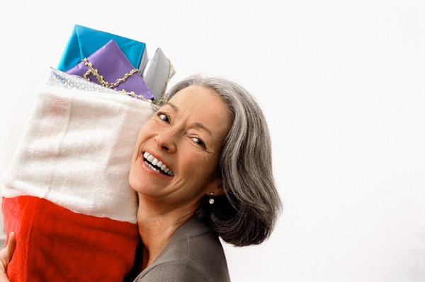 Mature woman holding a Christmas stocking --- Image by © Corbis